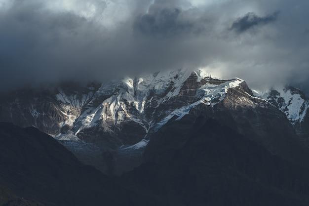 Bellissimo scatto della montagna dell'himalaya tra le nuvole Foto Gratuite