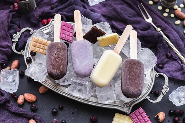 Bellissimo scatto di gelati vegani fatti in casa e barrette di cioccolato su cubetti di ghiaccio in una placca di metallo Foto Gratuite