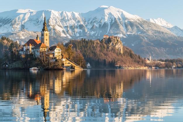 Bellissimo scatto di una casa vicino al lago con il monte ojstrica a bled, in slovenia Foto Gratuite