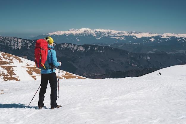 Bellissimo scatto di un uomo che fa un'escursione nelle montagne innevate dei carpazi in romania Foto Gratuite