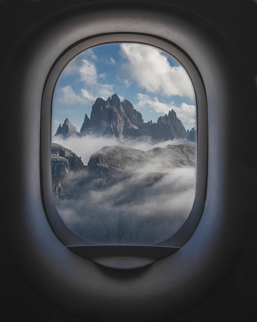Bella ripresa di montagne e un cielo nuvoloso dall'interno dei finestrini degli aerei Foto Gratuite