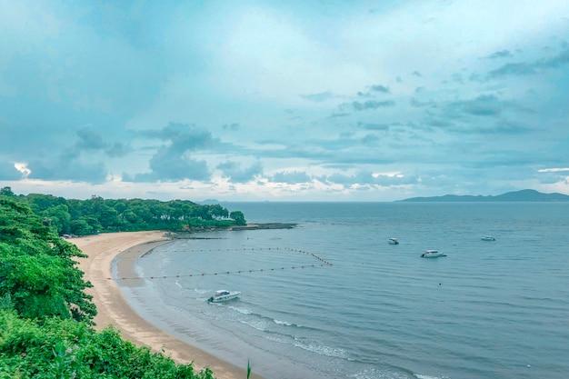 青い曇り空の下で水にボートでビーチの海岸の美しいショット 無料写真