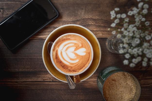 木製のテーブルに白いハートのパターンとカプチーノのカップの美しいショット 無料写真