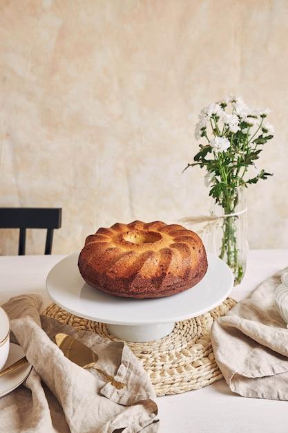 하얀 접시와 그 근처에 흰 꽃에 넣어 맛있는 링 케이크의 아름다운 샷 무료 사진