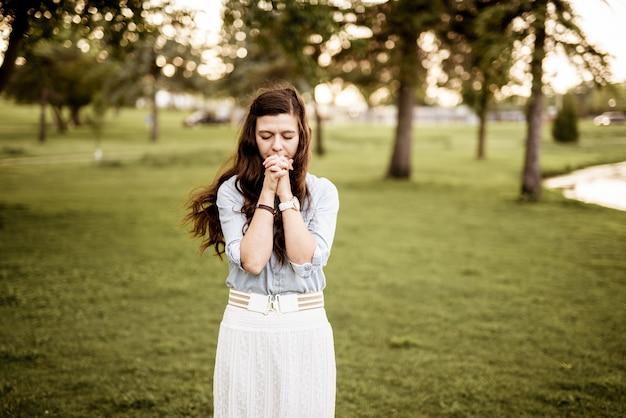 배경을 흐리게기도하면서 그녀의 입 근처에 그녀의 손으로 여성의 아름다운 샷 무료 사진