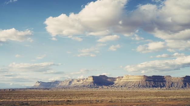 息をのむような雲と岩が多い丘の大きな砂漠の美しいショット 無料写真