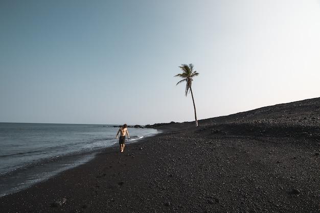 ヤシの木の近くの砂浜の海岸の上を歩く水着を着ている男性の美しいショット 無料写真