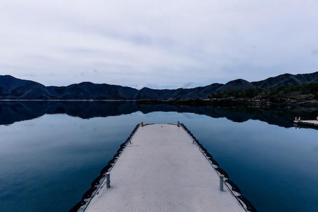 Красивая съемка пути на воде с горами на расстоянии под облачным небом Бесплатные Фотографии