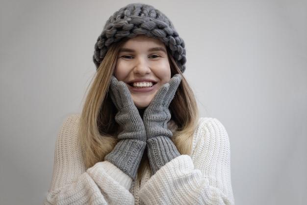 ニットの灰色の帽子と手袋を身に着けているかなり陽気な女性の美しいショット 無料写真