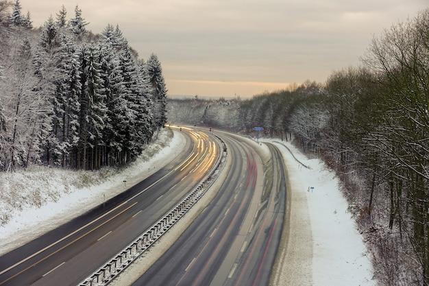 冬の間に雪に覆われた森の木々と道路の美しいショット 無料写真
