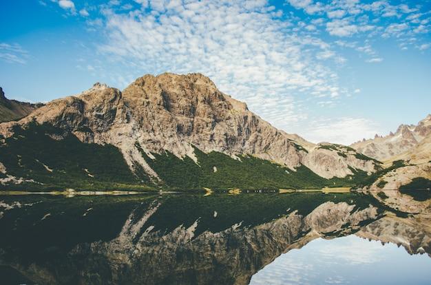 水の反射で湖の横にあるロッキーマウンテンの美しいショット 無料写真