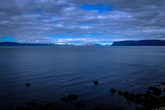 曇り空の下で遠くに海と山の美しいショット 無料写真