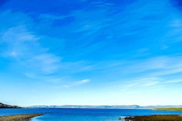 青い空の下で遠くに山と海の美しいショット 無料写真