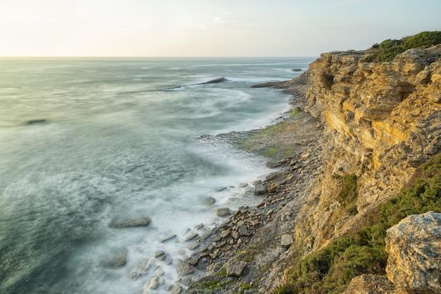 Красивый снимок берега моря с пейзажем заката в ясном небе Бесплатные Фотографии
