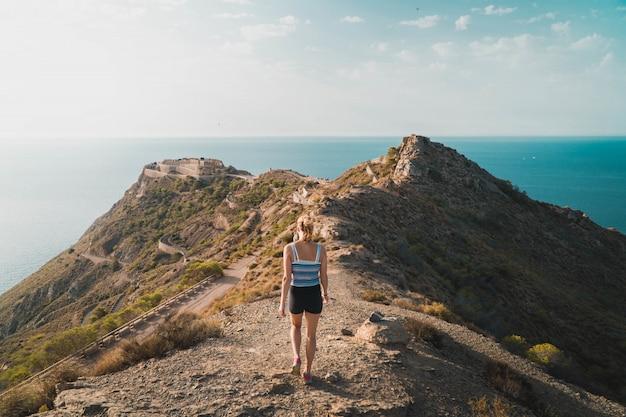 背景の晴れた空と海の横にある丘の上を歩く女性の美しいショット 無料写真