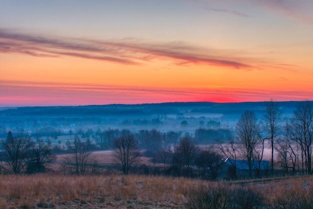 Красивый снимок удивительных красных и оранжевых облаков над большими туманными полями и лесом на рассвете Бесплатные Фотографии