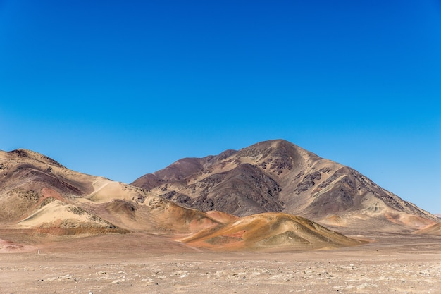 澄んだ青い空の下で遠くに山がある空のフィールドの美しいショット 無料写真