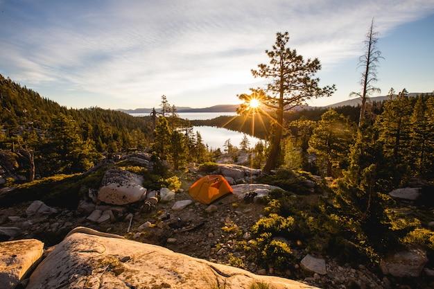 Красивая съемка оранжевого шатра на скалистой горе окруженной деревьями во время захода солнца Бесплатные Фотографии