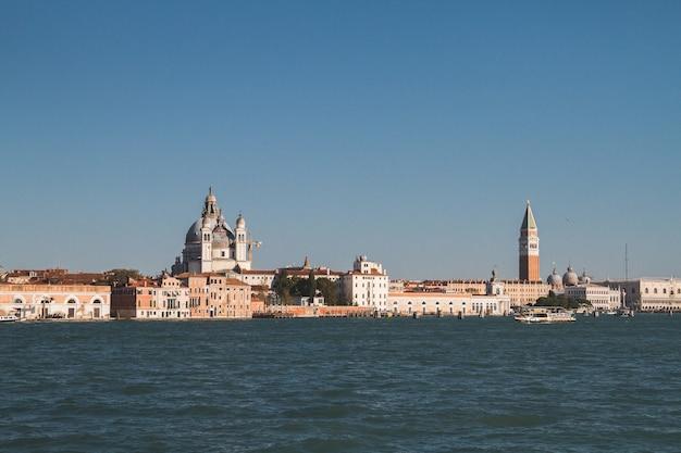 ヴェネツィアイタリア運河の距離にある建物の美しいショット 無料写真