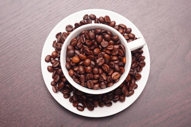 Красивый выстрел кофейных зерен в белой чашке и тарелке на деревянном столе Бесплатные Фотографии