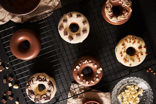 黒いテーブルの釉薬とチョコレートの部分で覆われたおいしいドーナツの美しいショット 無料写真