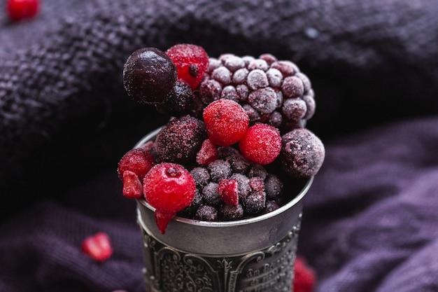 紫色の背景にアンティークシルバーカップで冷凍ベリーの美しいショット 無料写真