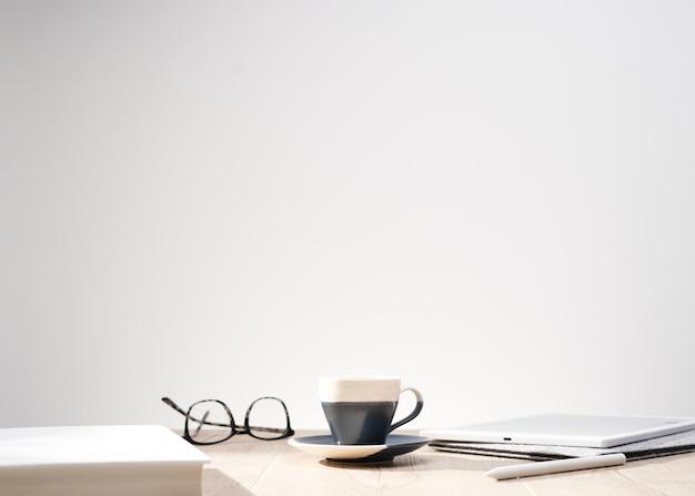 광학 안경 및 텍스트 흰색 배경 및 공간을 가진 테이블에 컵의 아름 다운 샷 무료 사진
