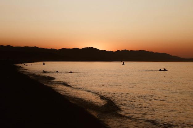 澄んだ空と海岸近くの水で泳ぐ人々の美しいショット 無料写真