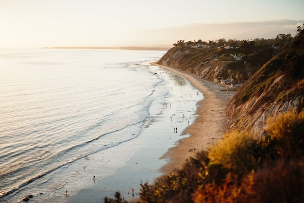 低い丘の隣の野生の海岸を歩いている人々の美しいショット 無料写真