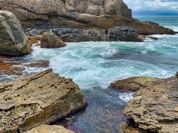 クレイジーな海の波がクラッシュする海の近くの岩の美しいショット 無料写真