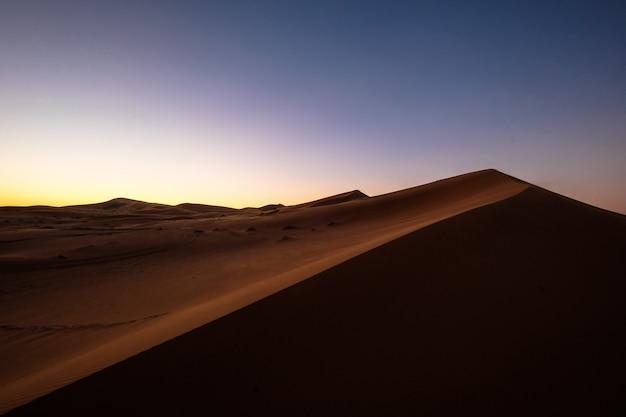 Красивый выстрел из песчаных дюн под фиолетовым и синим небом Бесплатные Фотографии