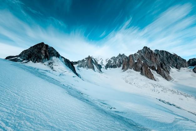 어두운 푸른 하늘이 눈 덮인 산의 아름다운 샷 무료 사진