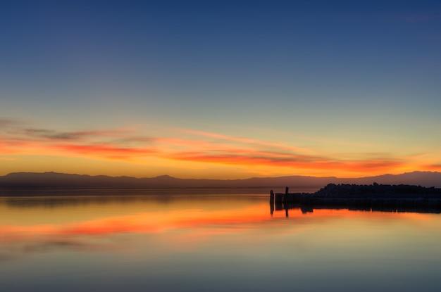 水の中のオレンジ色の夕焼け空の反射の美しいショット 無料写真