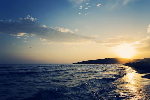 素晴らしい夕日と海の砂浜の海岸線の美しいショット 無料写真