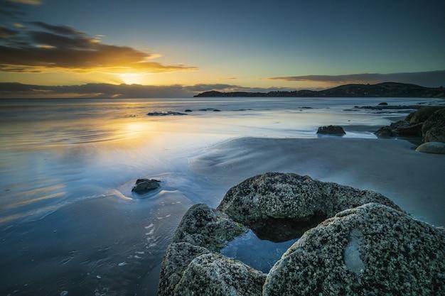 Красивый снимок моря с скалы и горы на расстоянии под синим и желтым небом Бесплатные Фотографии