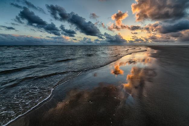 Красивый снимок заката, отражающего в море Бесплатные Фотографии