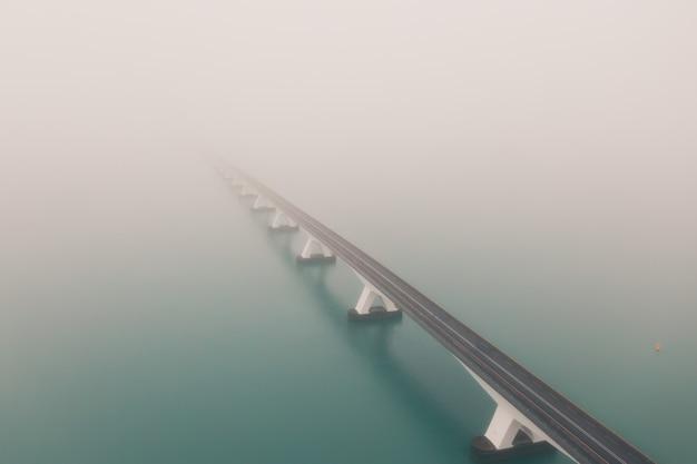 Красивый снимок моста в зеландии, покрытого туманом, в нидерландах Бесплатные Фотографии