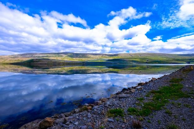 Красивый выстрел из воды возле скалистого берега и горы на расстоянии с облаками в небе Бесплатные Фотографии
