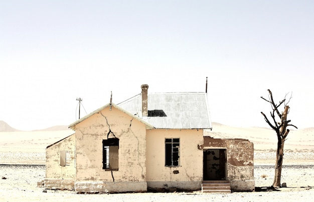 Beautiful shot of an old abandoned house in the middle of a desert near a leafless tree Free Photo