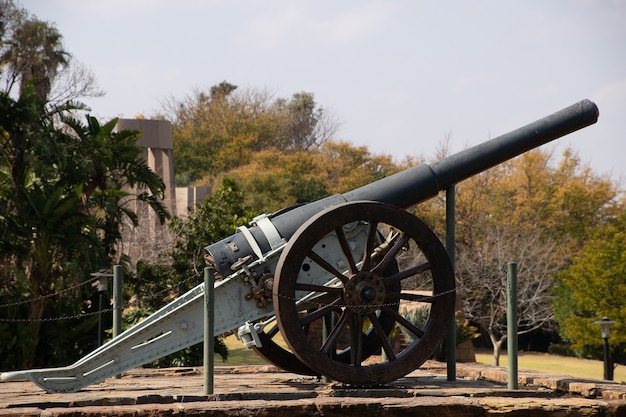 Bella ripresa di un vecchio cannone in un parco visualizzato in una giornata di sole Foto Gratuite