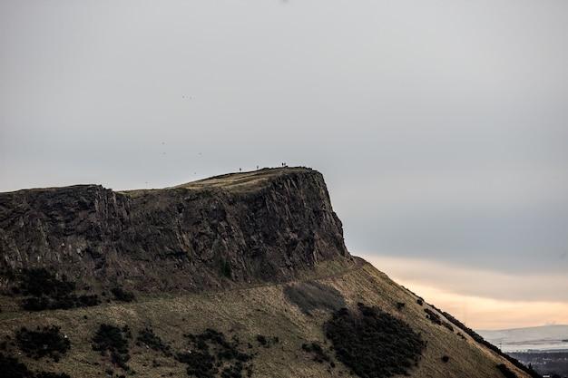 Bellissimo scatto di un popolo in piedi in cima alla scogliera in lontananza Foto Gratuite