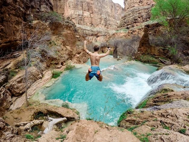 Bello colpo di una persona che indossa il costume da bagno che salta giù da una scogliera in acqua circondata da alberi Foto Gratuite