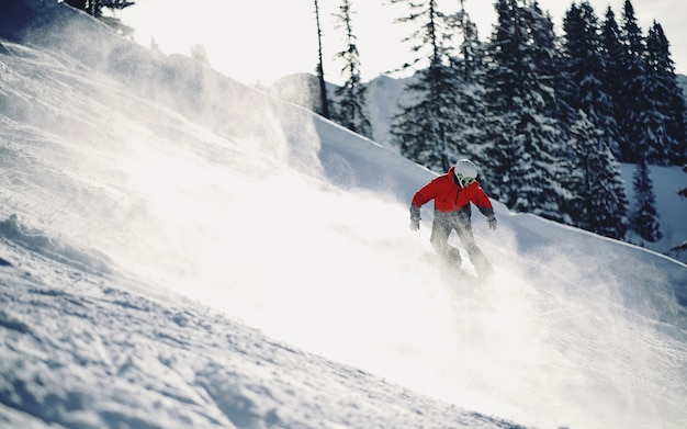 Beautiful shot of a person with red jacket skiing down the snowy mountain with blurred background Free Photo