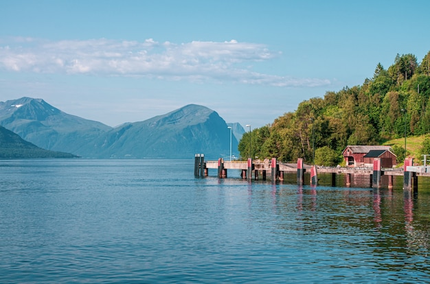 Beautiful shot of a pier on the sea near a tree forest surrounded by high mountains in norway Free Photo