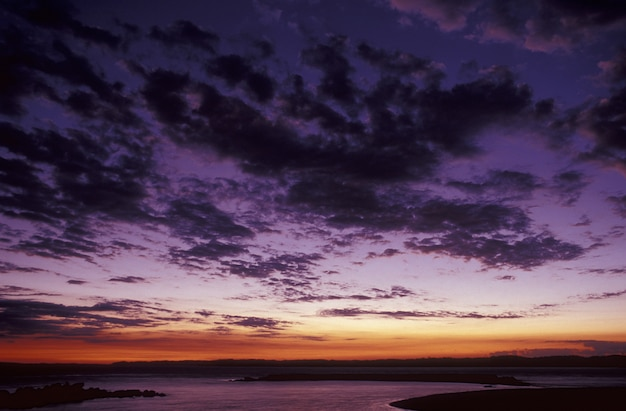 Beautiful shot of a purple sky with clouds above the sea at sunset Free Photo