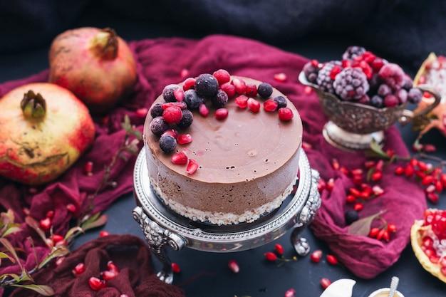 Bella ripresa di una torta vegana cruda con frutti di bosco e semi di melograno sparsi in giro Foto Gratuite