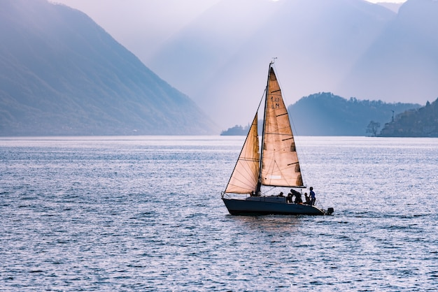 Beautiful shot of a sailing boat travelling across the sea surrounded by mountains Free Photo