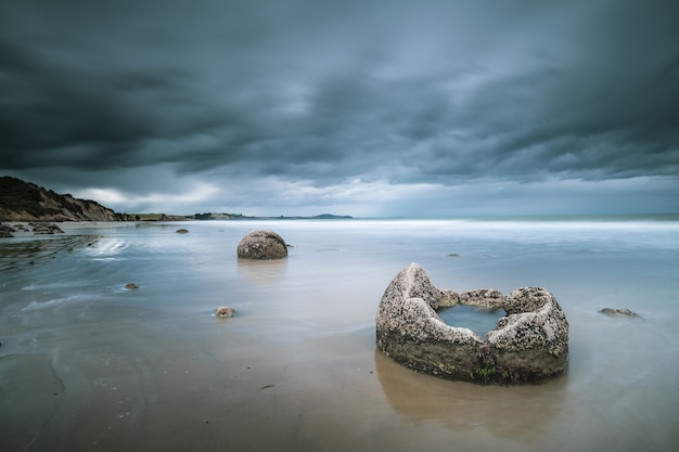 Beautiful shot of the sea with rocks and mountains in the distance under a blue cloudy sky Free Photo