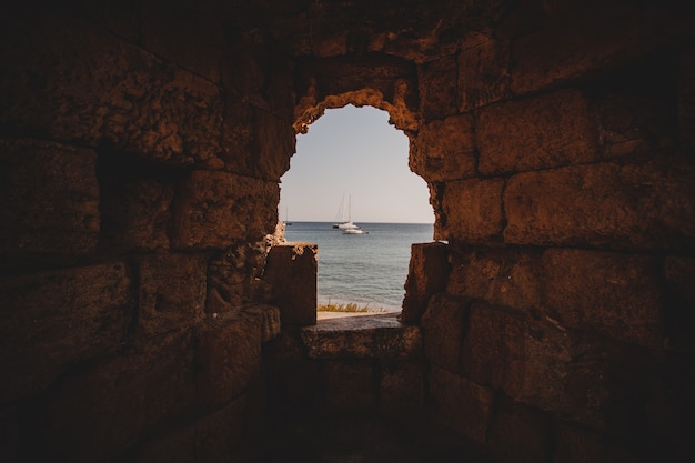 Beautiful shot of the sea with sailboats from the inside of a hole in a stone wall Free Photo
