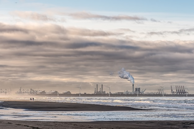 Beautiful shot of a sea with windmills and factory in the distance under a cloudy sky Free Photo